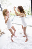 Two women jumping on bed Stock Images