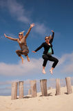 Two women jumping high on the beach Stock Images