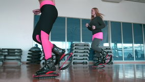 Two women jumping in kangoo shoes in the gym. Two women standing back to the mirror. Sporty women start running with kangoo shoes to the other side of the gym stock footage