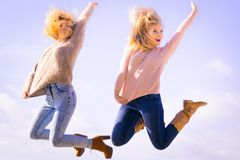 Two women jumping. Two women full of joy jumping around with sky in background. Female friends having fun outdoor Stock Photography