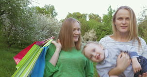 Two women with a kid walking in green park stock footage