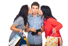Two women kiss sad man to give them money. Two women kissing sad resigned man cheeks to giving them money from his wallet for shopping  isolated on white Royalty Free Stock Images