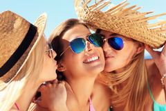 Two women kissing friend on the beach. A picture of two women kissing a friend on the beach party Royalty Free Stock Images