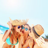 Two women kissing friend on the beach. A picture of two women kissing a friend on the beach party Stock Images