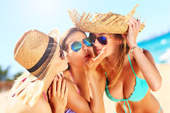 Two women kissing friend on the beach. A picture of two women kissing a friend on the beach party Royalty Free Stock Photo