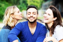 Two women kissing handsome man on his cheeks. Two beautiful women kissing handsome man on his cheeks royalty free stock photos
