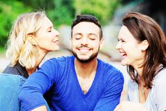 Two women kissing handsome man on his cheeks stock images