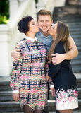 Two women kissing handsome smiling man in cheeks Royalty Free Stock Photography