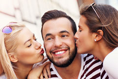 Two women kissing a man. A picture of two attractive women kissing a men in the city royalty free stock images