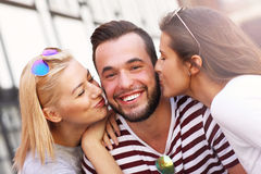Two women kissing a man. A picture of two attractive women kissing a men in the city stock photos