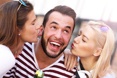 Two women kissing a man. A picture of two attractive women kissing a men in the city Stock Image