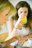 Two women in kitchen. A view of two women sitting at a kitchen table or counter, one drinking orange juice and coffee, the other reading the mail Stock Photo