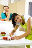 Two women in the kitchen cooking and eating happy. Gorgeous brunette women preparing healthy food Stock Photography