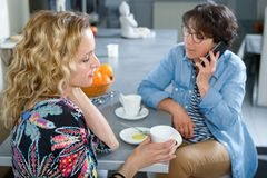Two women in kitchen drinking coffee and using smartphone. Two women in kitchen drinking coffee and using a smartphone Royalty Free Stock Photos