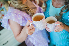 Two women in kitchen drinking a cup of tea. Two young women drinking tea in the beautiful aprons Stock Photos