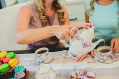 Two women in kitchen drinking a cup of tea. Two young women drinking tea in the beautiful aprons Royalty Free Stock Photography