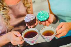 Two women in kitchen drinking a cup of tea. Two young women drinking tea in the beautiful aprons Royalty Free Stock Photo