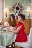 Two women in the kitchen drinking tea.  Stock Photos