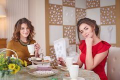 Two women in the kitchen drinking tea Stock Photo
