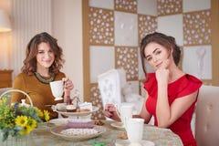 Two women in the kitchen drinking tea Stock Photo