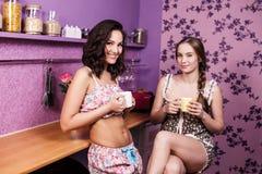 Two Women In Kitchen. Two Women Enjoying Hot Drink In Kitchen Stock Photo