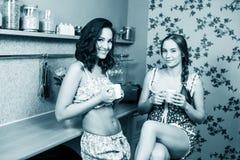 Two Women In Kitchen. Two Women Enjoying Hot Drink In Kitchen Royalty Free Stock Image