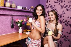 Two Women In Kitchen. Two Women Enjoying Hot Drink In Kitchen Royalty Free Stock Photography