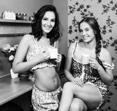 Two Women In Kitchen. Two Women Enjoying Hot Drink In Kitchen Royalty Free Stock Images