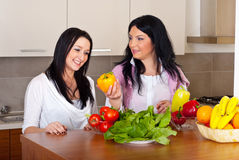 Two women in kitchen with fresh vegetables. Two women having conversation and one of them giving or showing a yellow paprika to her friend Royalty Free Stock Photos