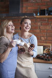 Two women in the kitchen. Mom, our muffins taste amazing Stock Photos