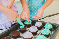 Two women in the kitchen preparing food. Two women in the kitchen making muffins.Kitchen interior Stock Image