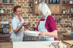 Two women in kitchen. Two women preparing ingredients for baking in kitchen Stock Photos