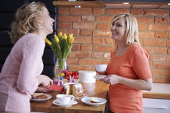Two women in the kitchen. Special moments of mother and daughter while Easter Stock Photos