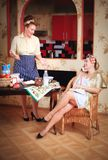 Two women in the kitchen. Work and relax, talking on the phone. Household scene, lifestyle. Household concept stock image