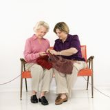 Two women knitting. stock photos