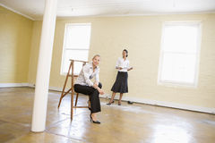 Two women with ladder in empty space Royalty Free Stock Photo