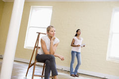 Two women with ladder in empty space holding paper Royalty Free Stock Images