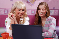 Two women with laptop. Two beautiful women with laptop at the kitchen Stock Images