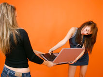 Two Women And A Laptop. Two young women on opposite sides of a laptop computer, both holding with both hands Royalty Free Stock Image