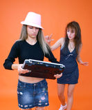 Two Women And A Laptop 3. One woman wearing a pink hat walking away with a laptop computer in her hands.  Second woman following behind with hand raised and Stock Images