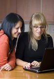 Two women on laptop royalty free stock photo