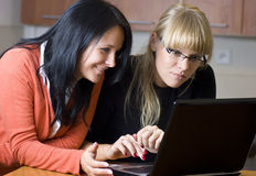 Two women on laptop. Two young women looking at the screen of a laptop computer. The look of surprise and amusement over their faces royalty free stock images