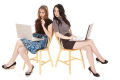 Two women laptops peeking Stock Images