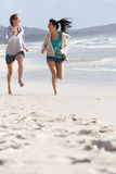 Two women laughing and running at the beach Stock Image