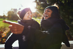 Two women laughing at something while standing in park Stock Photo