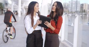 Two women laughing at a tablet computer. Two attractive stylish young women standing on a waterfront esplanade laughing at a tablet computer as they read stock footage