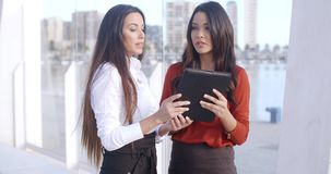 Two women laughing at a tablet computer. Two attractive stylish young women standing on a waterfront esplanade laughing at a tablet computer as they read stock video footage