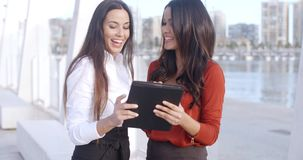 Two women laughing at a tablet computer. Two attractive stylish young women standing on a waterfront esplanade laughing at a tablet computer as they read stock video