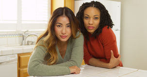 Two women leaning against kitchen counter looking at camera. At home Royalty Free Stock Photography