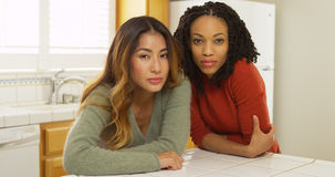 Two women leaning against kitchen counter looking at camera. At home Royalty Free Stock Images